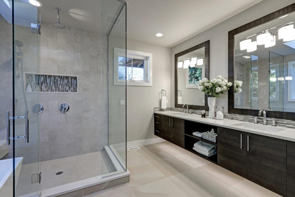 Spacious bathroom in gray tones with heated floors, walk-in shower, double sink vanity, and skylights