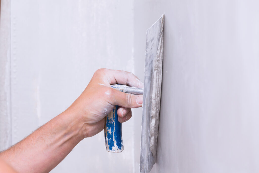 Handyman smoothing drywall before painting when renovating a house