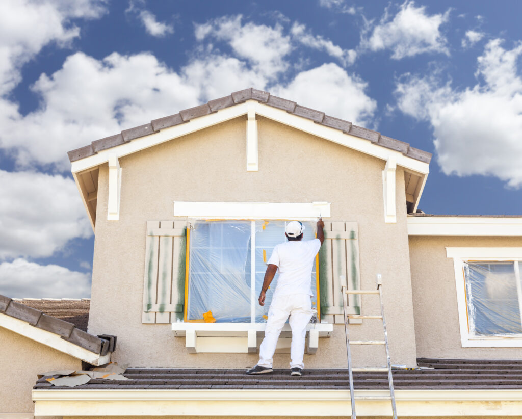 Busy house painter painting the trim and shutters of a home